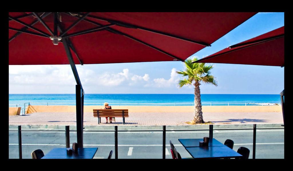 Ombrelloni rossi in primo piano con donna sulla panchina in riva al mare.